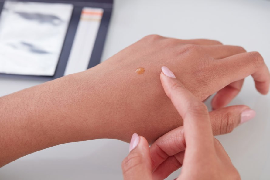 person rubbing skincare serum into her hand