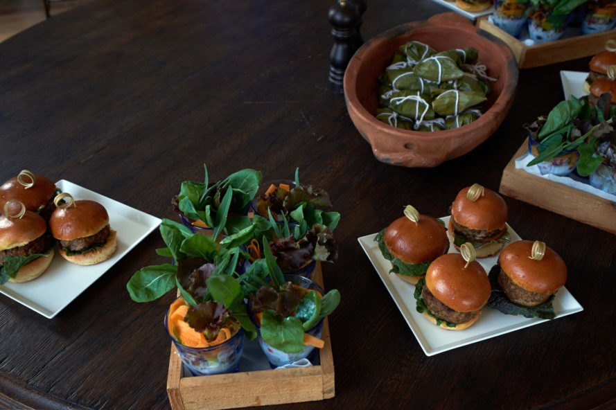 small burgers and salads on wood table