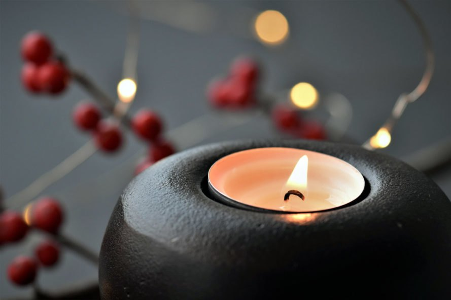 candle in gray holder with red berries in background