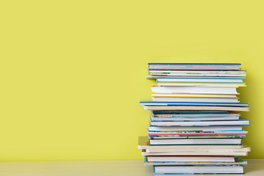 stack of children's books in front of yellow wall
