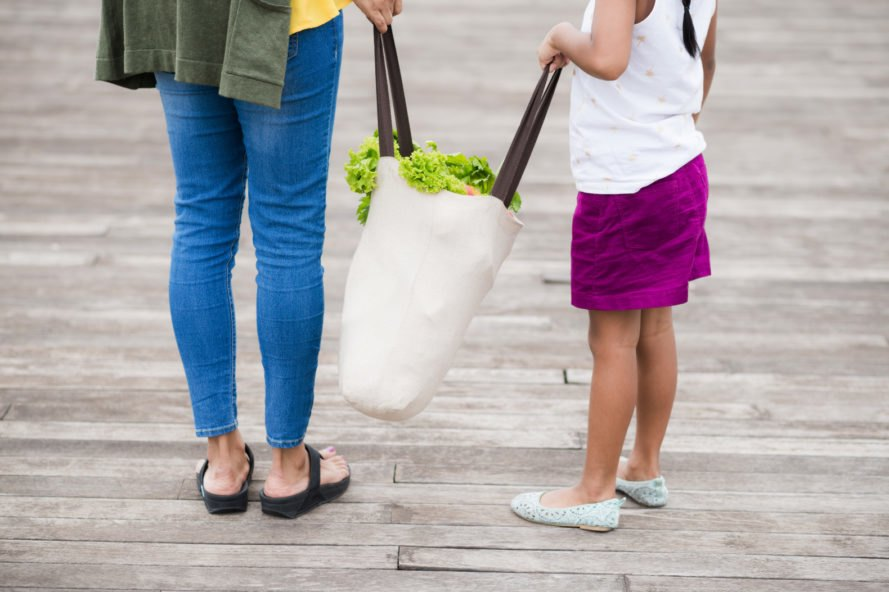 mother and daughter carrying a reusable grocery bag