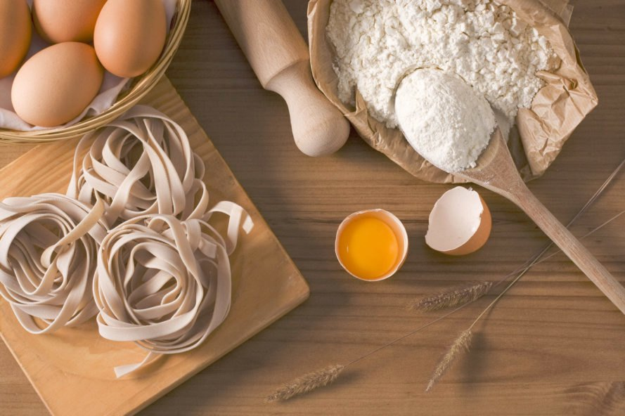 fresh pasta, brown eggs and flour on wood table