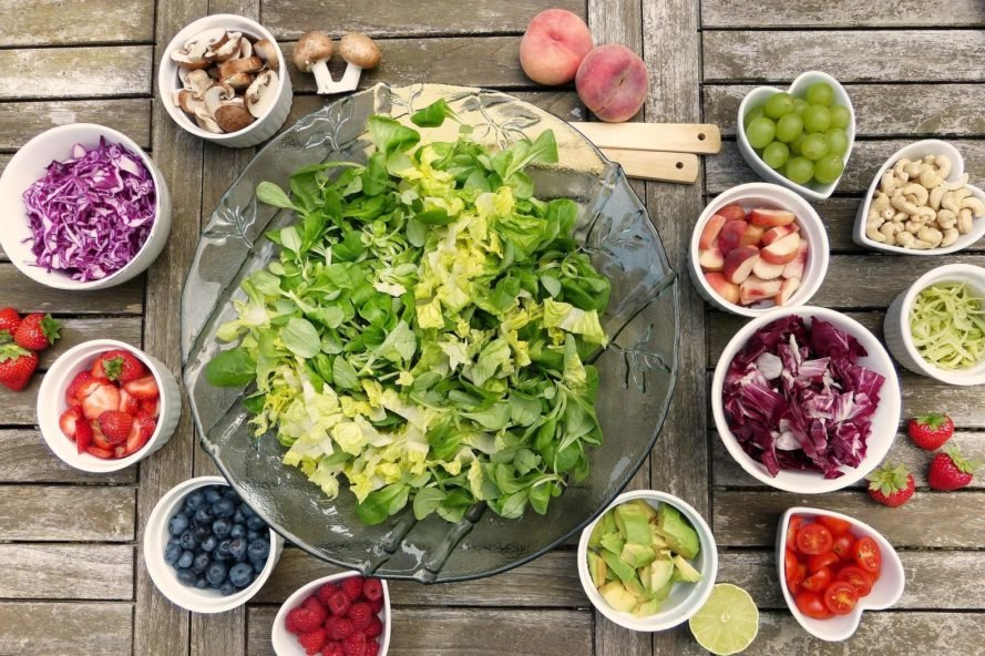 bowl of salad surrounded by bowls of salad toppings