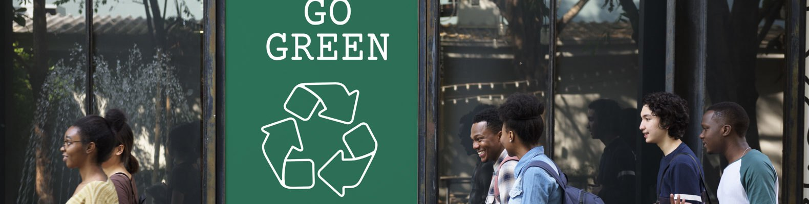 """people walking by sign that reads """"Go Green"""""""