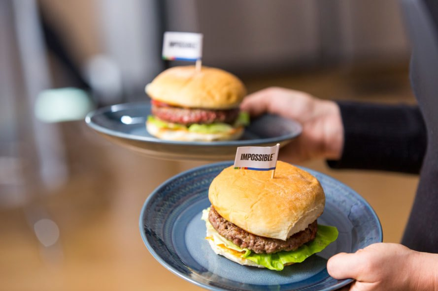 waiter serving Impossible plant-based burgers on plates