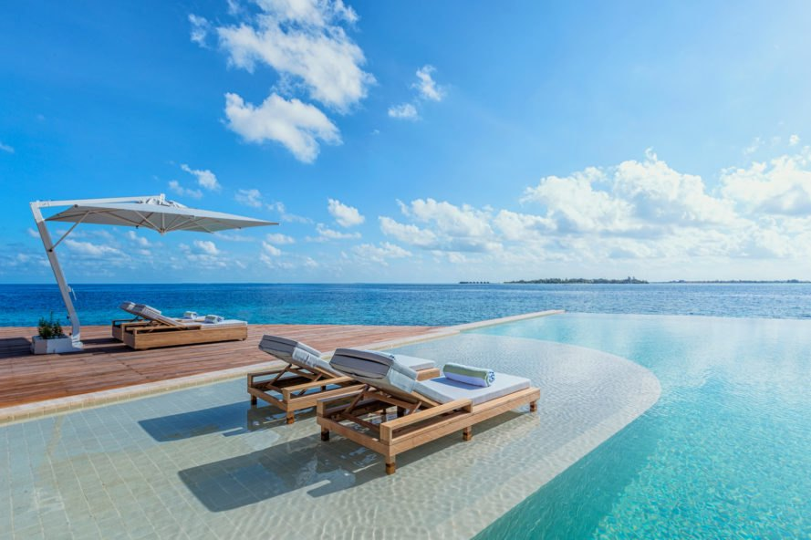 lounge chairs by an infinity pool looking over the ocean
