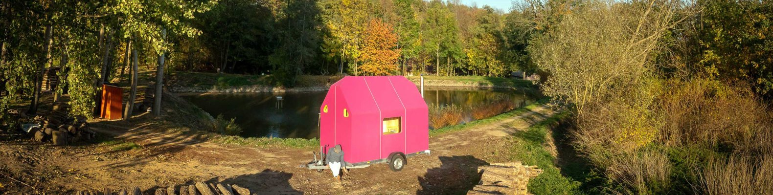 bright pink tiny home surrounded by trees in autumn