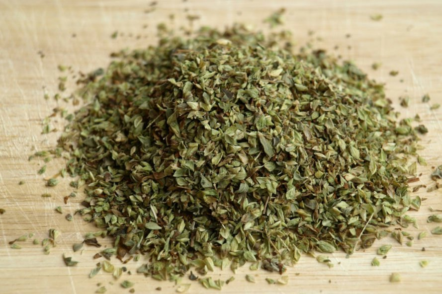 pile of dried oregano on wood table