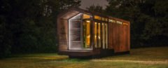 wood tiny home lit up at night