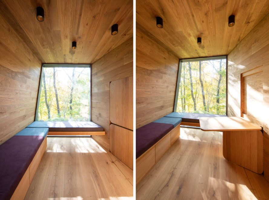 wood-lined cabin interior with long window seat and table folding out from the wall
