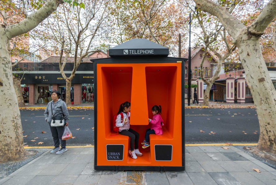 two children playing inside orange phone booth