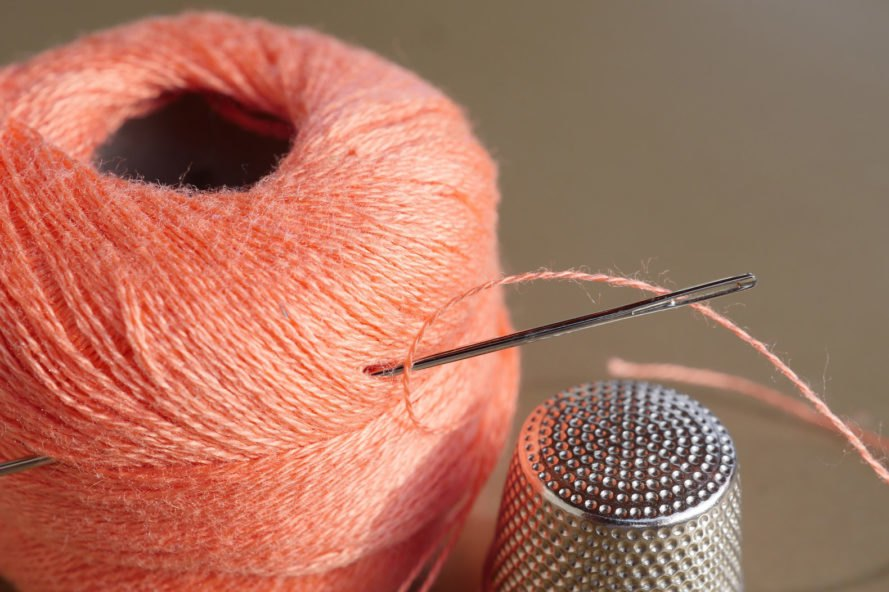 spool of pink thread with a needle and a thimble