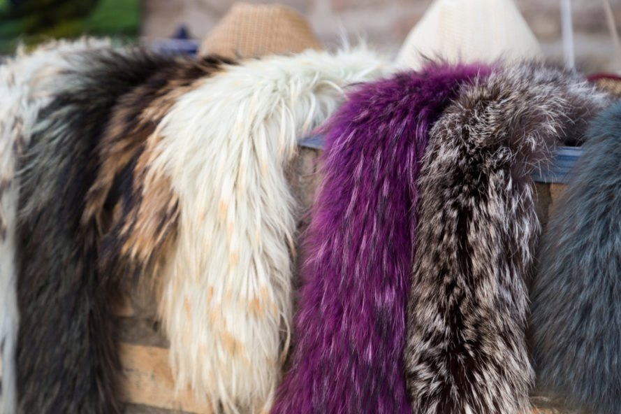 different colored faux fur scarves are hanged on a display rack