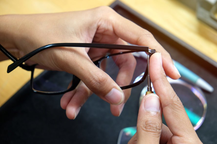 person repairing glasses