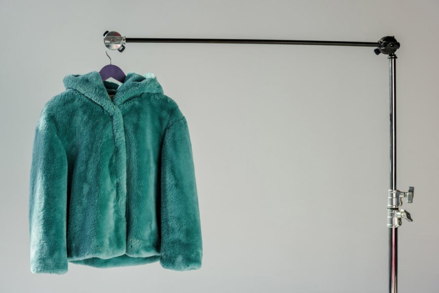 green faux fur jacket is hung on a display rack