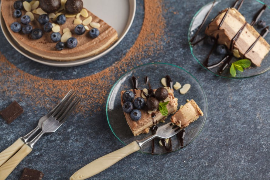 raw vegan chocolate cheesecake topped with almonds and blueberries