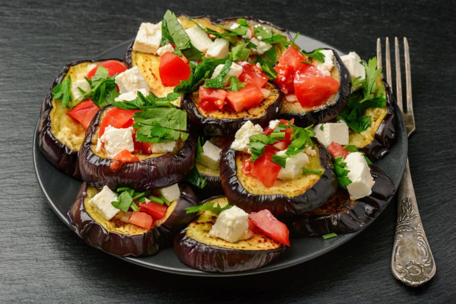 grilled eggplant slices topped with tomato, feta and fresh herbs