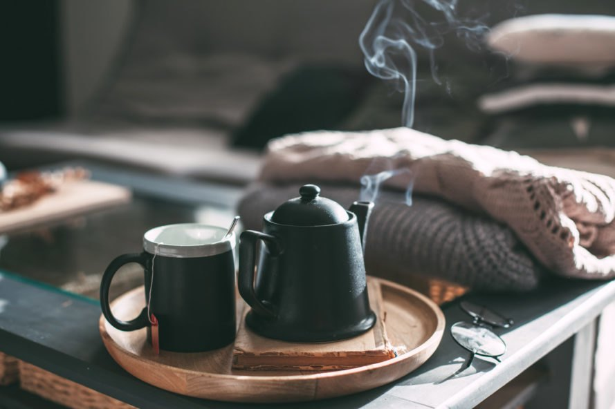 steaming tea pot and mug of tea on tray in a living room