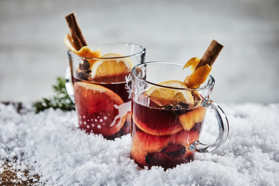 glass mugs filled with wassail in snow