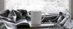 white coffee cup, book and blanket in front of window