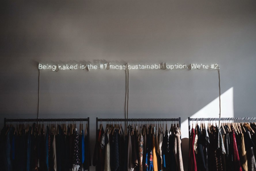 store with racks of clothing and neon sign on wall