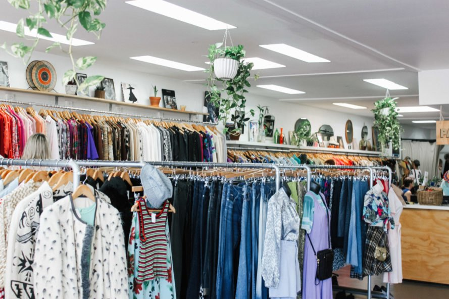 bright thrift store with racks of clothes and hanging plants