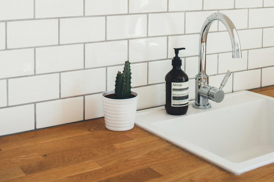 white sink in kitchen with succulent and subway tiled wall