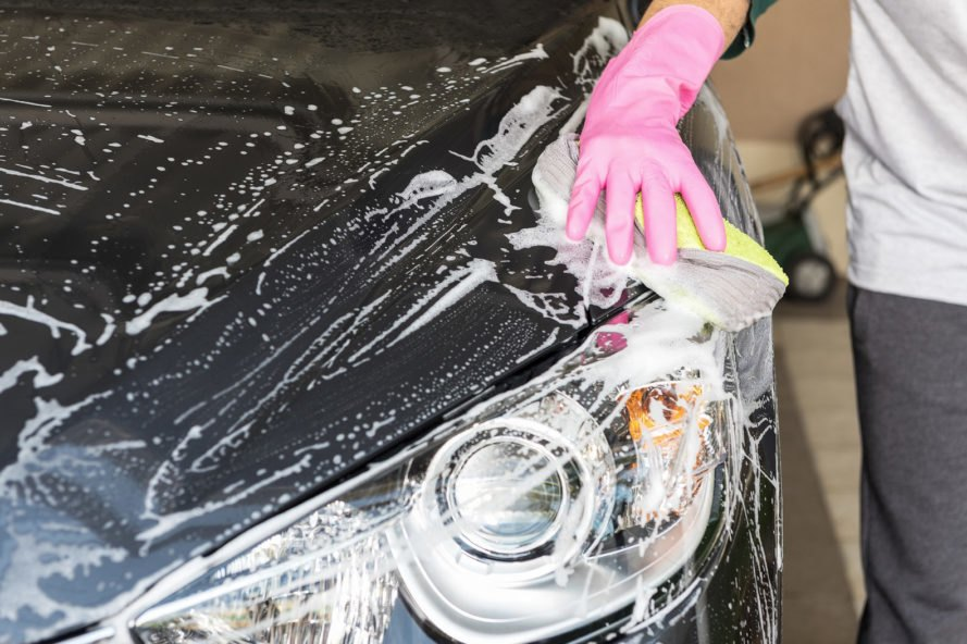 person hand-washing a black car