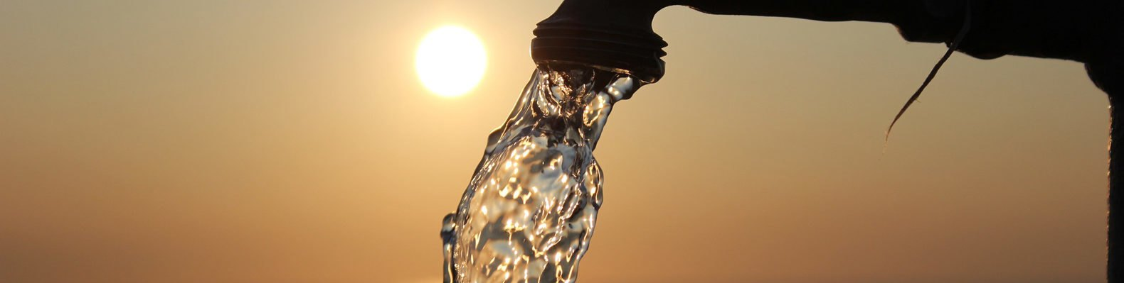 outdoor faucet running water at sunset