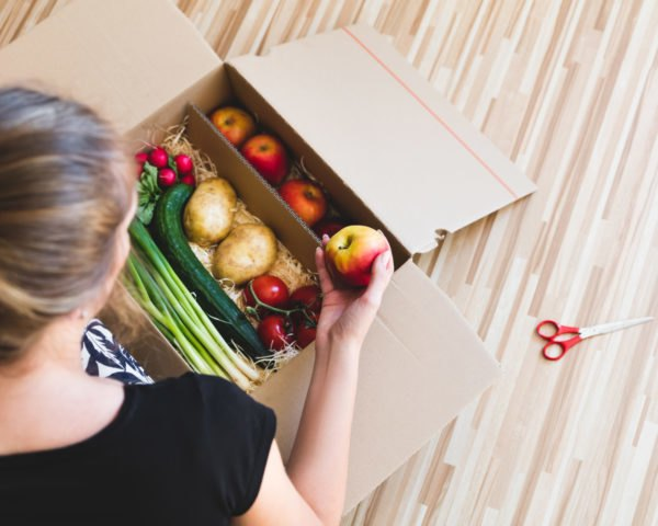 woman looking at box of produce