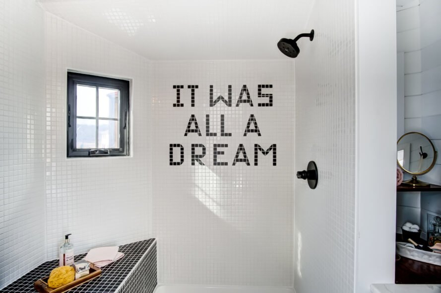 "bathroom with writing on the tiles that reads ""It Was All A Dream"""