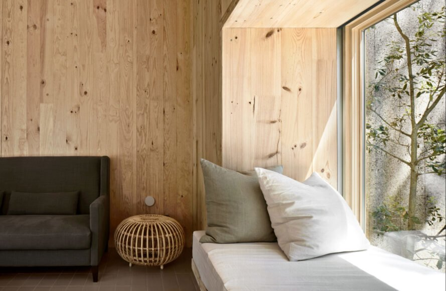 an interior wall with light-hued panels and a seating space