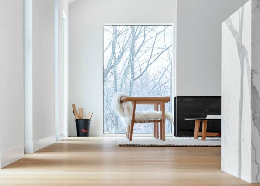 a white room with wooden floors and windows revealing views of snowy landscape