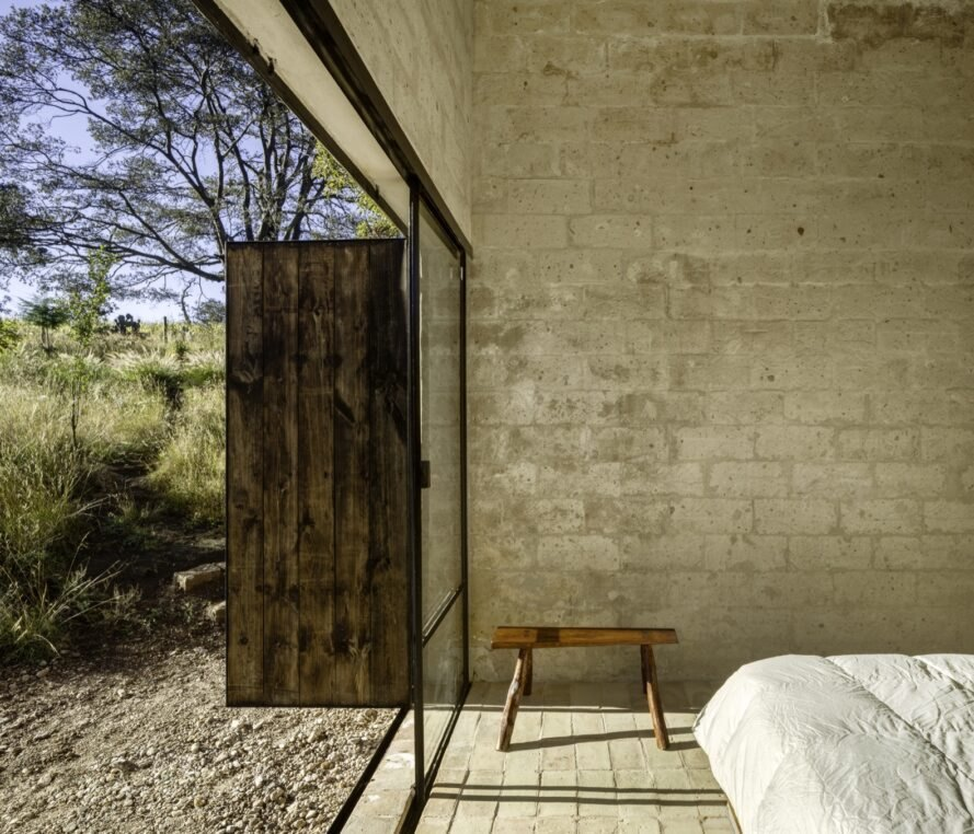 bedroom with stone walls and open wooden doors to the outside
