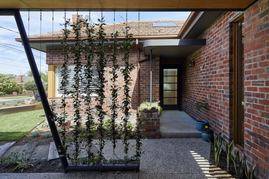 brick lines the home's exterior with plants surrounding the entrance