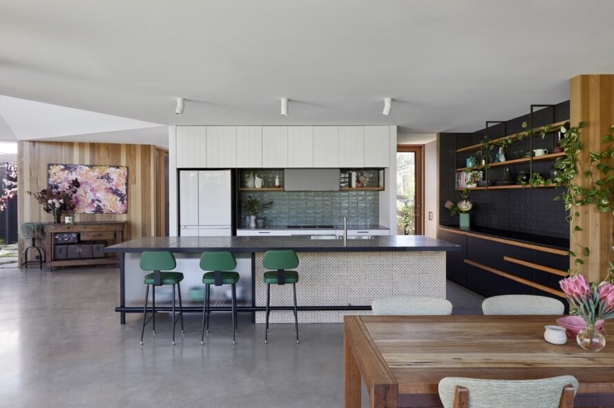 white kitchen cabinets with green tiles and surrounding black painted brick and wood