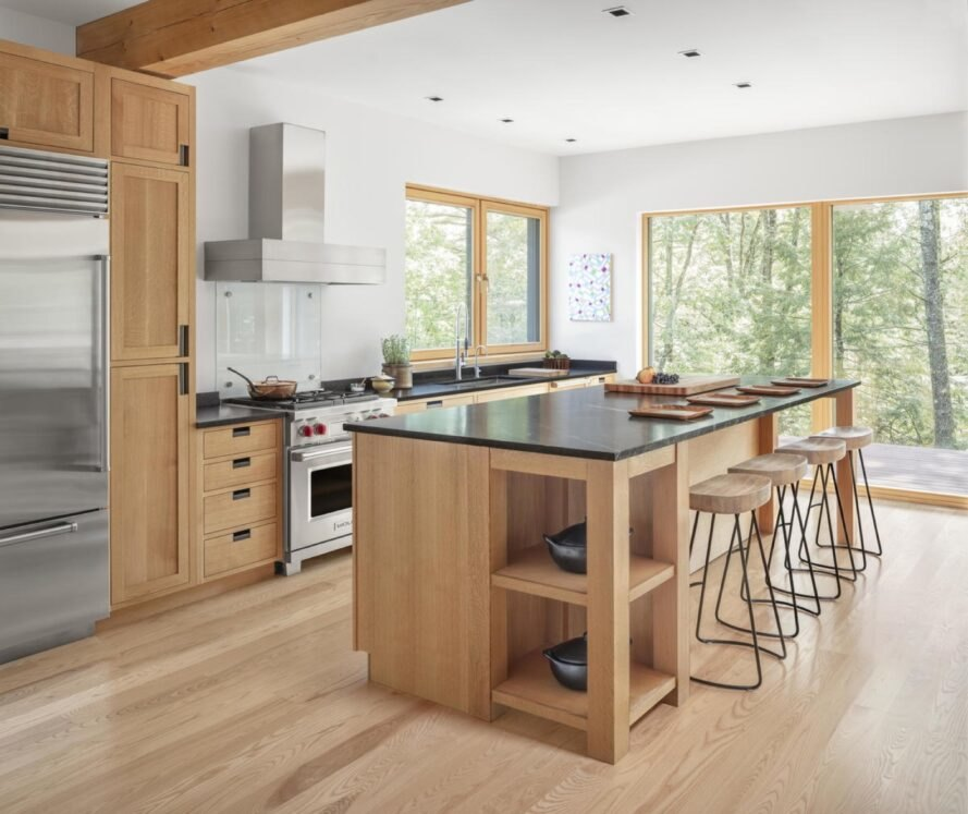 kitchen with light brown wood floors matching with cabinets with large windows letting sunlight into the home