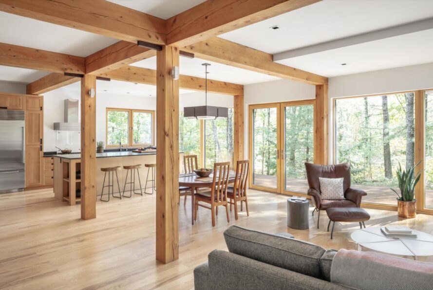 living room with plenty of large windows and wood floors and beams and neutral colored furniture