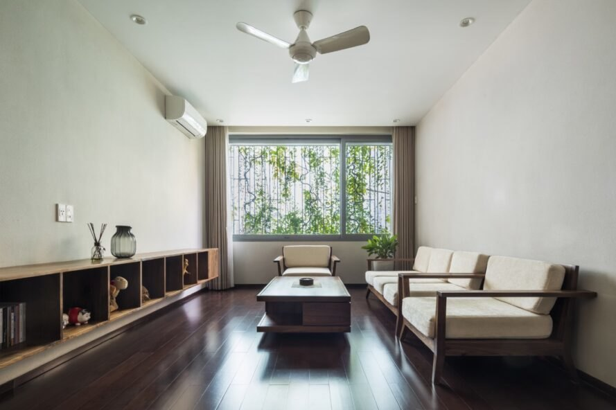 white living area with cream couches and a glass wall covered in plants