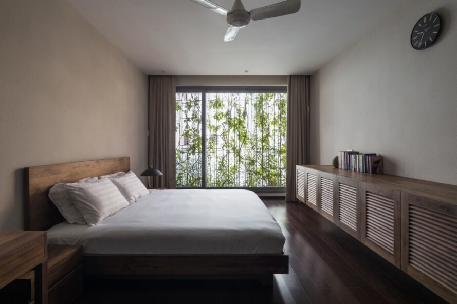 bedroom with large white bed and glass wall covered in plants