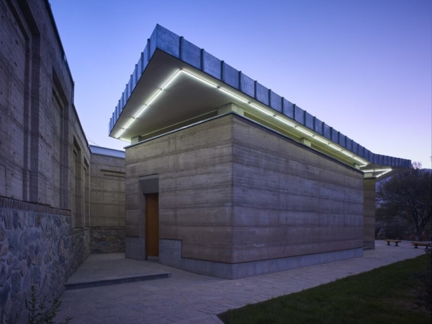 rammed earth building with green lighting