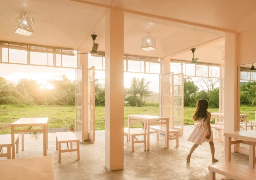 girl in white dress walks by tables and chairs
