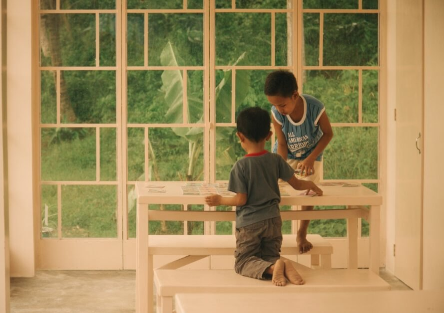 two little boys work on crafts on wood table