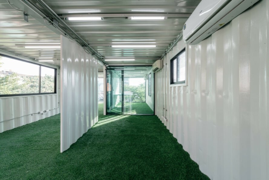 interior of shipping container building with white walls and grass-like floors