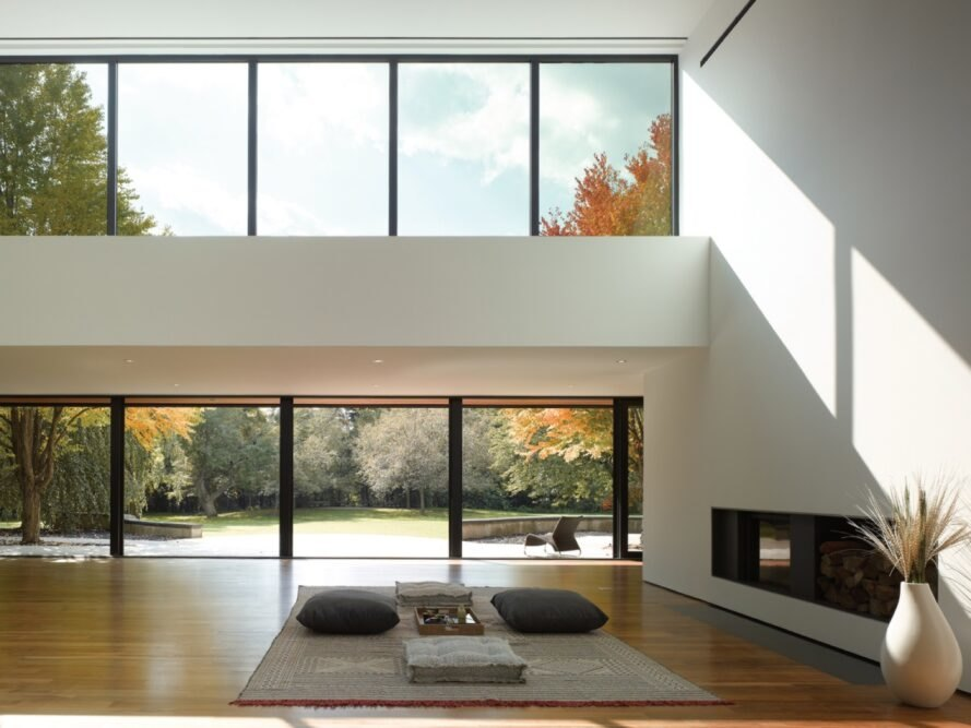 white room with several glass windows and a modern fireplace