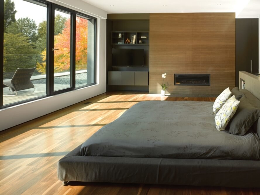 bedroom with gray bed and wood floors