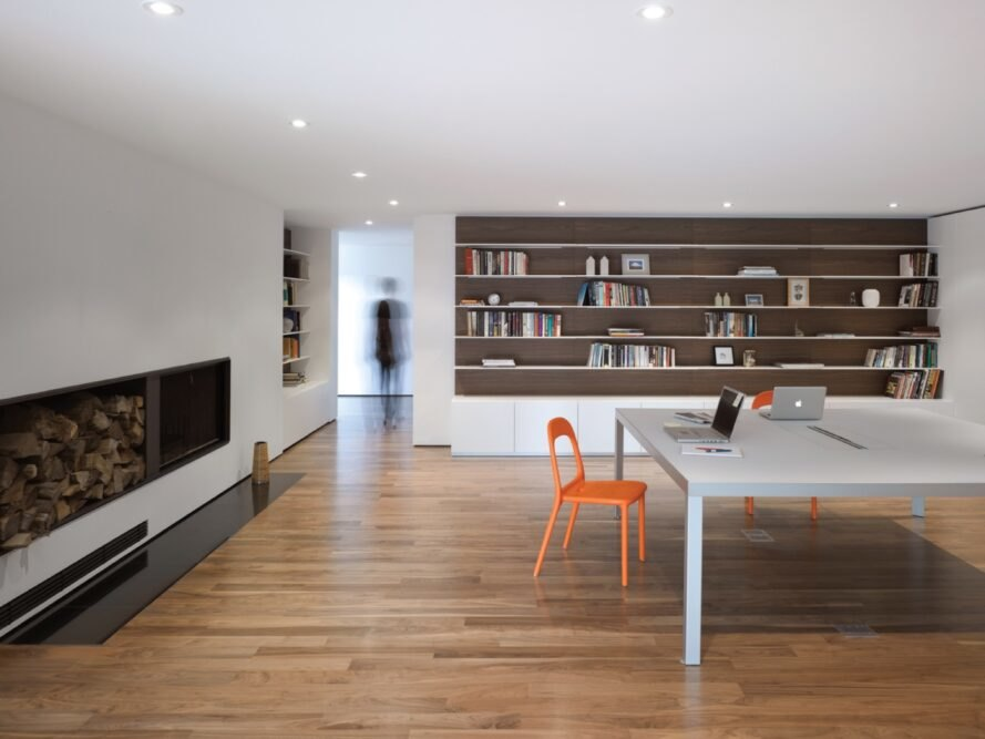 white room with large gray table and bookshelves