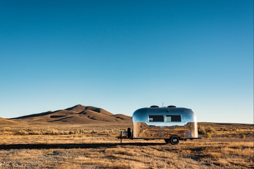 silver airstream trailer in a desert landscape