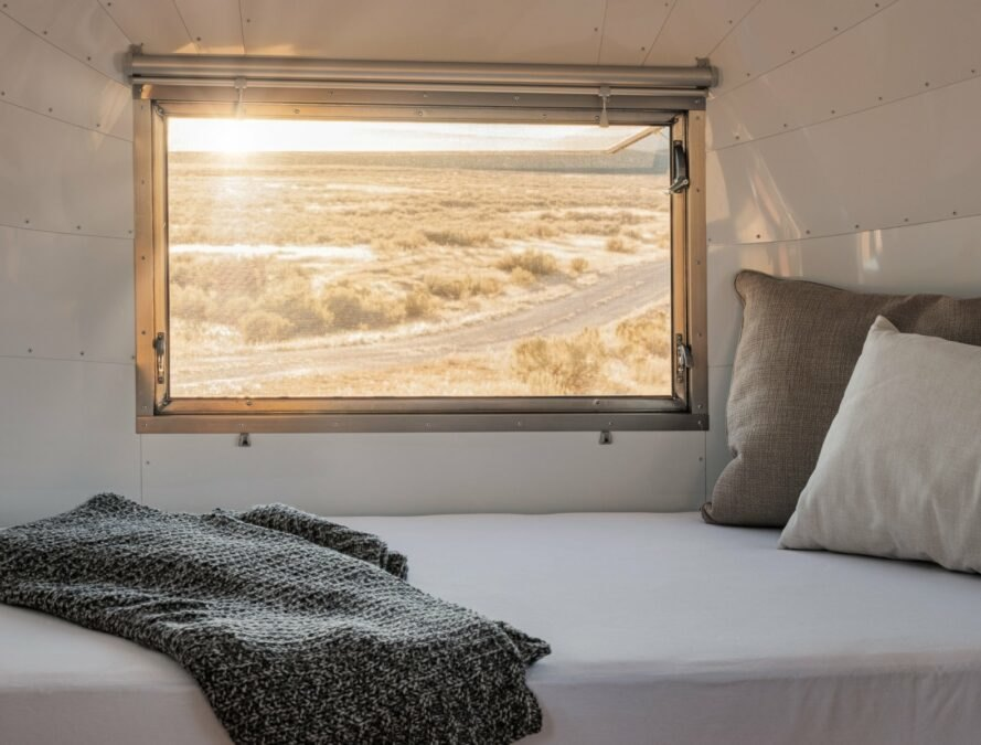 bedroom in airstream trailer with sunlight coming through a large window