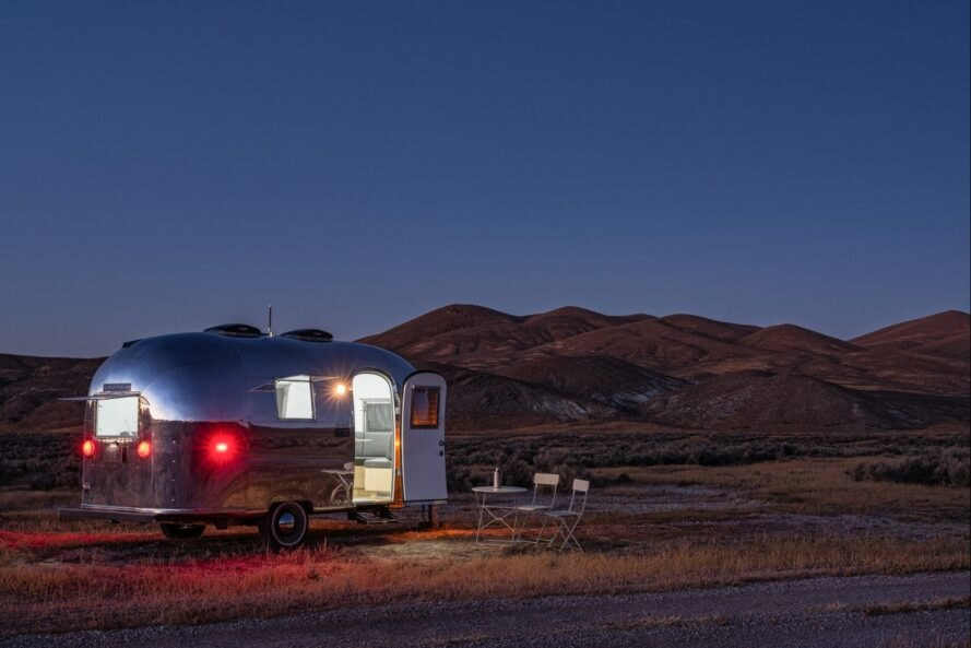 silver airstream trailer with door open at night